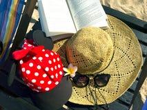 Κόκκινη ΚΑΠ με τα άσπρα σημεία Πόλκα, καπέλο αχύρου, λουλούδια, βιβλίο και τραγουδημένος Στοκ Εικόνες