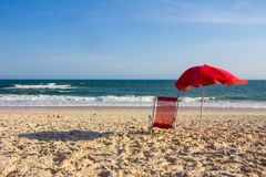 Κόκκινη καρέκλα και κόκκινη ομπρέλα μια ηλιόλουστη ημέρα στην παραλία Στοκ φωτογραφία με δικαίωμα ελεύθερης χρήσης