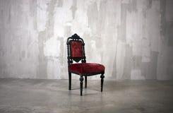 Κόκκινη καρέκλα πίσω από τον γκρίζο τοίχο Στοκ Εικόνες