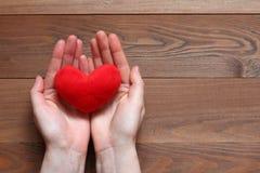 Κόκκινη καρδιά βελούδου στα θηλυκά χέρια Στοκ Εικόνες