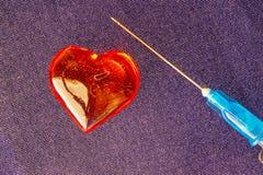 Κόκκινη καρδιά γυαλιού κοντά στη βελόνα, η επεξεργασία του ειδυλλίου Στοκ φωτογραφία με δικαίωμα ελεύθερης χρήσης