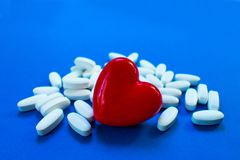 Κόκκινη καρδιά με τα χάπια Έννοια των καρδιακών παθήσεων στοκ εικόνα