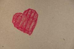Κόκκινη καρδιά που επισύρεται την προσοχή σε ένα υπόβαθρο χαρτονιού Στοκ φωτογραφίες με δικαίωμα ελεύθερης χρήσης