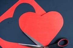 Κόκκινη καρδιά που χαράζεται από το φύλλο εγγράφου και το ψαλίδι χάλυβα στο σκοτεινό pai Στοκ εικόνα με δικαίωμα ελεύθερης χρήσης