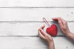 Κόκκινη καρδιά σε ετοιμότητα μια κορδέλλα και θηλυκά, άσπρο ξύλινο υπόβαθρο σανίδων βαλεντίνος ημέρας s Τοπ άποψη, διάστημα αντιγ στοκ φωτογραφία