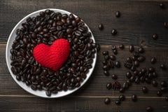Κόκκινη καρδιά σε πολύ ψημένο υπόβαθρο φασολιών καφέ στο άσπρο πιάτο στον ξύλινο πίνακα Ισχυρό μαύρο espresso, σιτάρια της πλάτης στοκ φωτογραφία με δικαίωμα ελεύθερης χρήσης