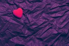 Κόκκινη καρδιά τοπ άποψης στο ζαρωμένο σκοτεινό πορφυρό υπόβαθρο σύστασης Έννοια ημέρας και αγάπης του ευτυχούς βαλεντίνου Ρομαντ στοκ εικόνες