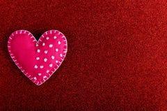 Κόκκινη καρδιά φιαγμένη από αισθητός σε ένα κόκκινο υπόβαθρο Χειροποίητο κενό για τη ευχετήρια κάρτα, διάστημα αντιγράφων στοκ εικόνα