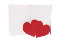 Κόκκινη καρδιά εγγράφου ζεύγους στο κενό ανοικτό βιβλίο που απομονώνεται στο λευκό στοκ φωτογραφίες