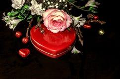 Κόκκινη καρδιά κιβωτίων με τις σοκολάτες και ανθοδέσμη από τα άσπρα λουλούδια Στοκ Εικόνες