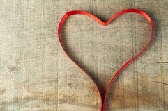 Κόκκινη καρδιά κορδελλών στην ξύλινη ανασκόπηση Στοκ φωτογραφίες με δικαίωμα ελεύθερης χρήσης