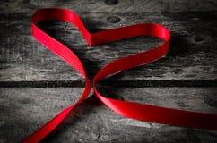 Κόκκινη καρδιά κορδελλών στο μαύρο ξύλινο υπόβαθρο, πλάτη ημέρας βαλεντίνων Στοκ φωτογραφία με δικαίωμα ελεύθερης χρήσης