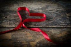 Κόκκινη καρδιά κορδελλών στο ξύλινο υπόβαθρο, υπόβαθρο ημέρας βαλεντίνων Στοκ Εικόνες