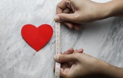 Κόκκινη καρδιά με τα χέρια γυναικών που κρατούν τη μέτρηση της ταινίας Στοκ Φωτογραφία