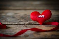 Κόκκινη καρδιά με την κορδέλλα στο ξύλινο υπόβαθρο, ΤΣΕ ημέρας βαλεντίνων Στοκ Εικόνες