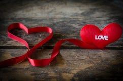 Κόκκινη καρδιά με την κορδέλλα στο ξύλινο υπόβαθρο, ΤΣΕ ημέρας βαλεντίνων Στοκ Φωτογραφίες