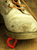 Κόκκινη καρδιά που συντρίβεται από μια βαριά, παλαιά στρατιωτική μπότα Στοκ Εικόνες