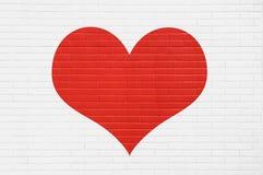 Κόκκινη καρδιά σε έναν άσπρο τουβλότοιχο άνδρας αγάπης φιλιών έννοιας στη γυναίκα Στοκ φωτογραφία με δικαίωμα ελεύθερης χρήσης