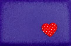 Κόκκινη καρδιά στο πορφυρό εκλεκτής ποιότητας υπόβαθρο δέρματος Στοκ εικόνα με δικαίωμα ελεύθερης χρήσης