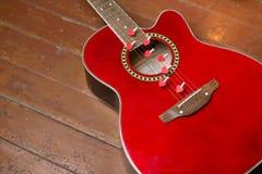 Κόκκινη κιθάρα με τις καρδιές, σημειώσεις αγάπης στις σειρές Στοκ Φωτογραφίες