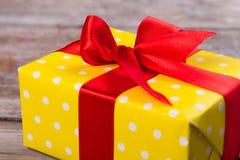 Κόκκινη κορδέλλα μεταξιού σε ένα κίτρινο δώρο Στοκ εικόνες με δικαίωμα ελεύθερης χρήσης