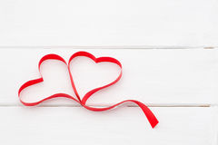 Κόκκινη κορδέλλα με μορφή των καρδιών στο άσπρο ξύλινο υπόβαθρο ανασκόπησης η μπλε κιβωτίων καρδιά δώρων ημέρας έννοιας εννοιολογ Στοκ Φωτογραφίες