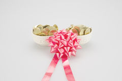 Κόκκινη κορδέλλα με το σωρό των χρυσών νομισμάτων στο κεραμικό φλυτζάνι Στοκ Εικόνα