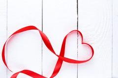 Κόκκινη κορδέλλα μορφής καρδιών στον άσπρο πίνακα Στοκ Φωτογραφία
