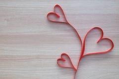 Κόκκινη κορδέλλα μορφής καρδιών τρία στην ξύλινη επιφάνεια με το διάστημα για το κείμενο Στοκ φωτογραφία με δικαίωμα ελεύθερης χρήσης