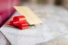 Κόκκινη κορδέλλα στο γαμήλιο κιβώτιο παρόν Στοκ Εικόνες