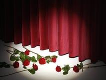 Κόκκινη κουρτίνα θεάτρων στη σκηνή με τα κόκκινα τριαντάφυλλα στοκ φωτογραφία