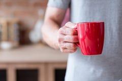 Κόκκινη κούπα λαβής ατόμων προγευμάτων ποτών πρωινού καυτή στοκ εικόνες με δικαίωμα ελεύθερης χρήσης
