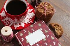 Κόκκινη κούπα Χριστουγέννων με τον καφέ και μπισκότα στον ξύλινο πίνακα Στοκ Εικόνες