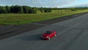 Κόκκινη μετατρέψιμη οδήγηση αυτοκινήτων εμπρός _ απόθεμα βίντεο