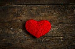 Κόκκινη μορφή καρδιών που γίνεται από το μαλλί στο παλαιό shabby ξύλινο υπόβαθρο Στοκ Εικόνες