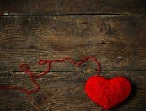 Κόκκινη μορφή καρδιών που γίνεται από το μαλλί στο παλαιό shabby ξύλινο υπόβαθρο Στοκ εικόνες με δικαίωμα ελεύθερης χρήσης
