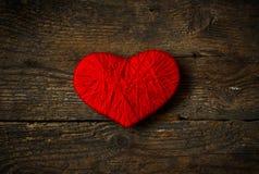 Κόκκινη μορφή καρδιών που γίνεται από το μαλλί στο παλαιό shabby ξύλινο υπόβαθρο Στοκ Φωτογραφία