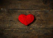 Κόκκινη μορφή καρδιών που γίνεται από το μαλλί στο παλαιό shabby ξύλινο υπόβαθρο Στοκ εικόνα με δικαίωμα ελεύθερης χρήσης