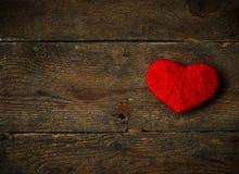 Κόκκινη μορφή καρδιών που γίνεται από το μαλλί στο παλαιό shabby ξύλινο υπόβαθρο Στοκ Φωτογραφίες