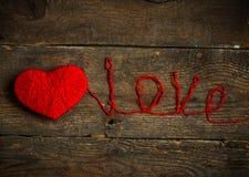 Κόκκινη μορφή καρδιών ewith μια αγάπη επιγραφής που γίνεται από το μαλλί σε παλαιό Στοκ εικόνες με δικαίωμα ελεύθερης χρήσης