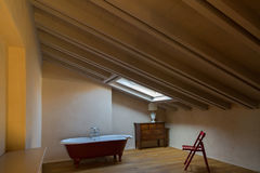 Κόκκινη μπανιέρα κάτω από το παράθυρο στο αττικό δωμάτιο, δίπλα στην κόκκινη ξύλινη καρέκλα Στοκ Φωτογραφία