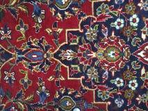 Κόκκινη μπλε περσική κουβέρτα στο πάτωμα με τις διάφορες μορφές στοκ φωτογραφίες