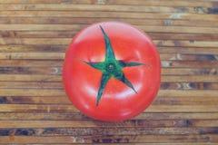 Κόκκινη ντομάτα στο πιάτο μπαμπού Στοκ Φωτογραφία