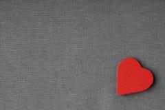 Κόκκινη ξύλινη διακοσμητική καρδιά στο γκρίζο γκρίζο υπόβαθρο υφασμάτων. στοκ εικόνα