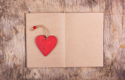 Κόκκινη ξύλινη καρδιά και ένα ανοικτό βιβλίο με τις κενές σελίδες στο παλαιό ξύλινο υπόβαθρο Σελιδοδείκτες και βαλεντίνος του ξύλ στοκ φωτογραφία με δικαίωμα ελεύθερης χρήσης