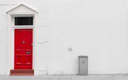 Κόκκινη ξύλινη πόρτα με την ασημένια αυλάκωση πορτών ταχυδρομείου και τα ρόπτρα πορτών Στοκ εικόνα με δικαίωμα ελεύθερης χρήσης