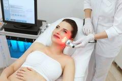 Κόκκινη οδηγημένη ελαφριά επεξεργασία Γυναίκα που κάνει την του προσώπου θεραπεία δερμάτων στοκ εικόνες