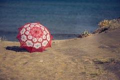 Κόκκινη ομπρέλα υφάσματος δαντελλών στην παραλία στο υπόβαθρο της θάλασσας Κόκκινη ομπρέλα στην άμμο Στοκ Εικόνα