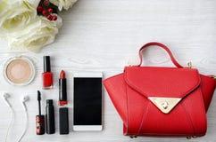 Κόκκινη ουσία ομορφιάς στον άσπρο ξύλινο πίνακα με την τσάντα στοκ εικόνα