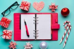 Κόκκινη παρούσα σημείωση κιβωτίων και εγγράφου με το μήνυμα Χαρούμενα Χριστούγεννας: Ho Ho Ho! θέση στον πίνακα γραφείων με το la Στοκ εικόνα με δικαίωμα ελεύθερης χρήσης